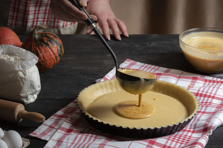 Cropped Hands Of Woman Pouring Liquid On Dough In Kitchen