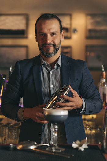 Male bartender preparing cocktail at bar counter