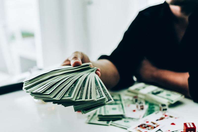 Midsection of businessman holding us paper currency while playing cards on table