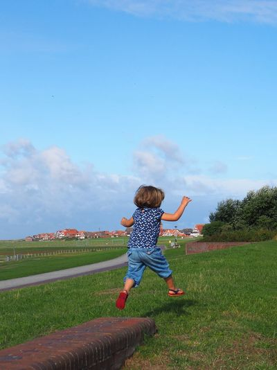 Full Length Child Grass Childhood Sky One Person Nature Casual Clothing Girls Leisure Activity Arms Outstretched Excitement Arms Raised Real People Blue Summer Jump Jumping Flying Northsea Happiness Running Green Eastfrisian East Frisian Islands