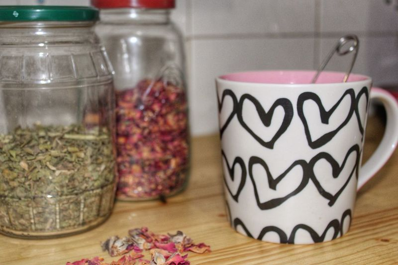Close-up of coffee cup and jar of herbs