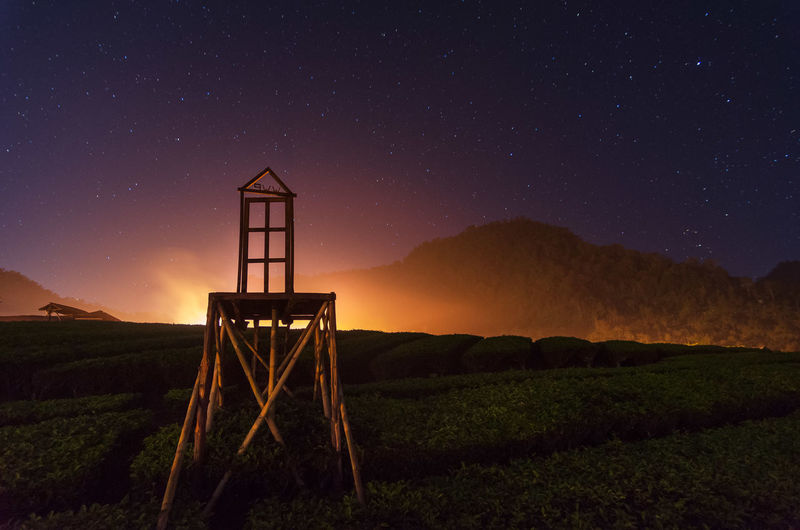 Lifeguard hut on field against sky at night