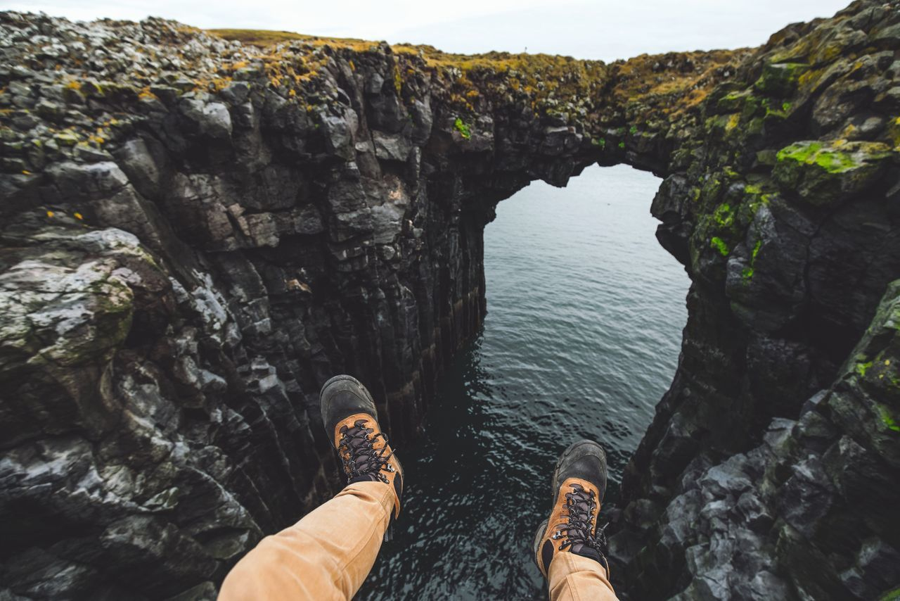 Low section of person sitting on cliff by sea