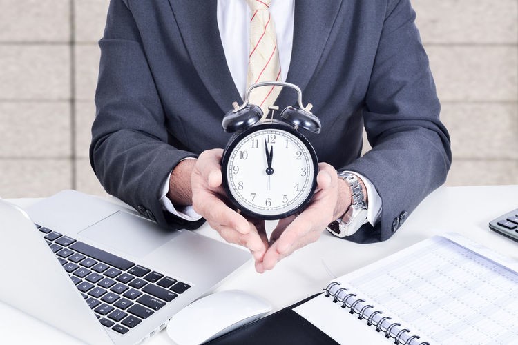 Businessman holding a clock.Business concept. Adult Business Businessman Clock Computer Day Desk Human Hand Indoors  Laptop Men Occupation One Person People Real People Sitting Suit Technology Time Using Laptop Watch Well-dressed Wireless Technology Working