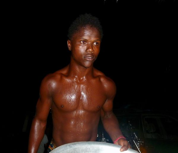 Shirtless Young Man Standing Outdoors At Night