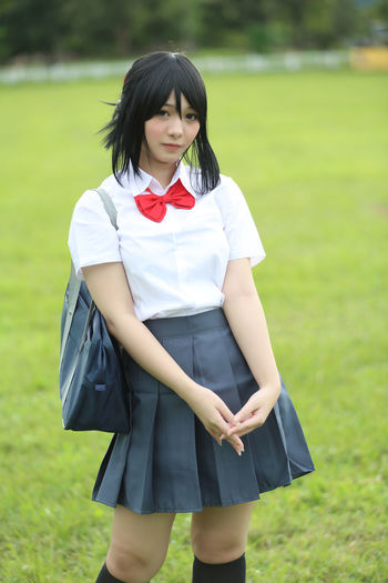 Portrait Of Young Woman In School Uniform Standing In Park