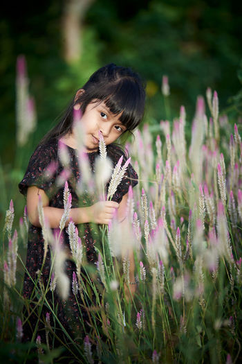 Close-up of woman on purple flowering plants on field
