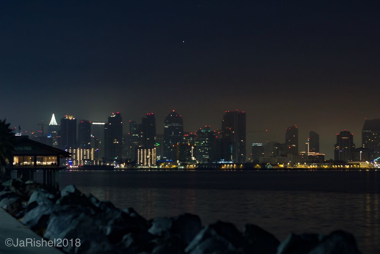 skyscraper, architecture, city, building exterior, cityscape, built structure, modern, night, illuminated, sky, city life, urban skyline, travel destinations, outdoors, sea, water, no people, nature