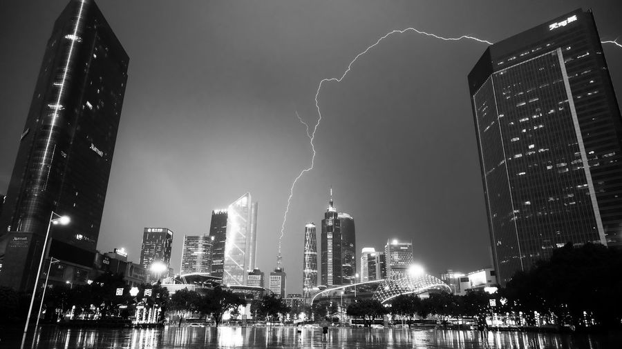 Low Angle View Of Lightning Against Sky Over Illuminated Cityscape At Night
