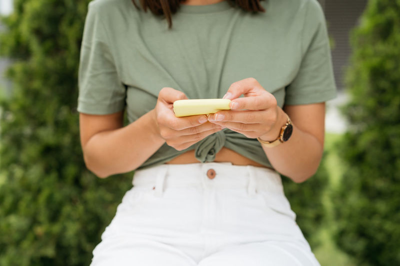 Midsection of woman holding mobile phone