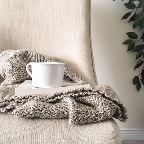 Cup with book placed on sofa