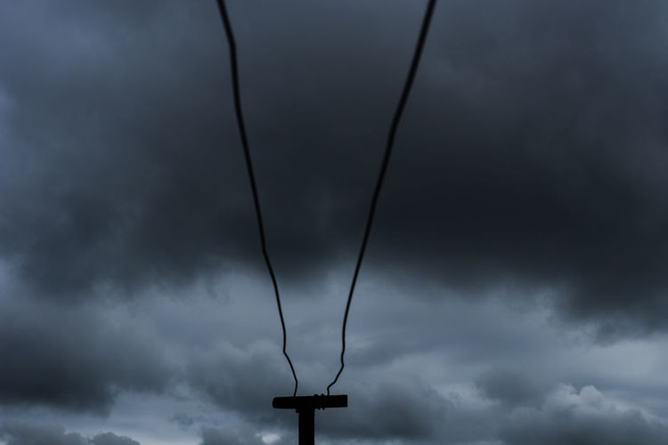 Low angle view of silhouette telephone pole against sky