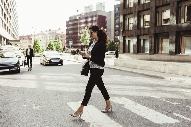 Full length side view of man walking on city street