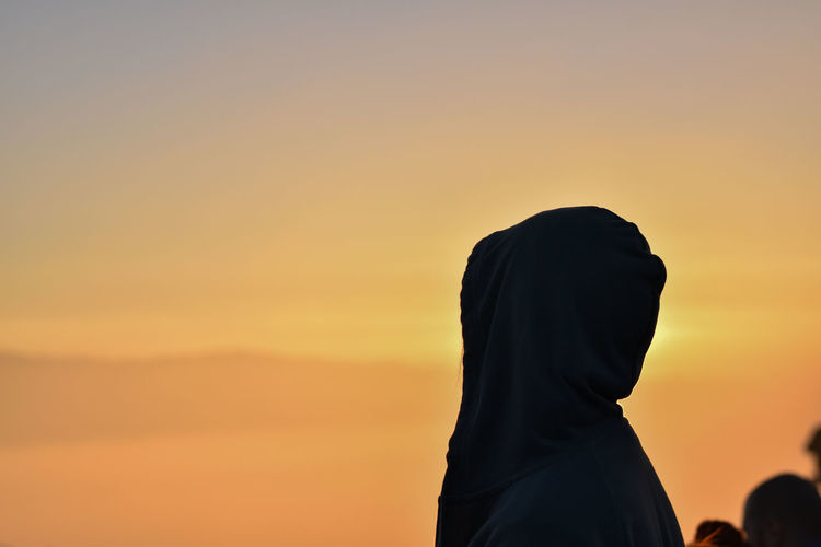Woman wearing headscarf against sky during sunset