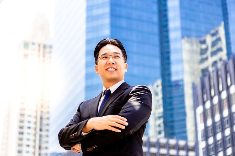 Smiling businessman with arms crossed standing against buildings in city