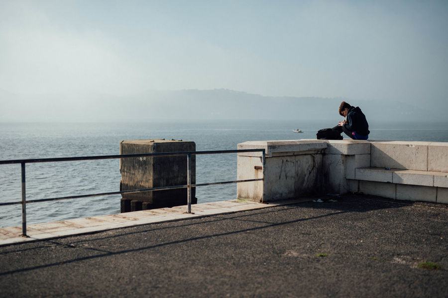 Alone City City Life Contemplation Foggy Lisboa Lisbon Lisbon - Portugal Lonesome One Man Only One Person Outdoors Railing Relaxation Sea Single Sitting Sitting Outside Urban Landscape Vacation Warm Water Young Adult