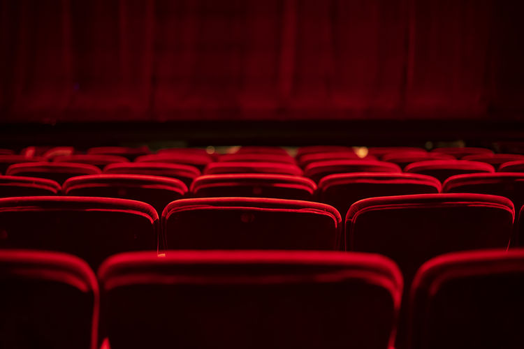 Red seats and curtains of an empty theater Red In A Row Seat Arts Culture And Entertainment Indoors  Movie Theater Empty Film Industry No People Absence Chair Repetition Auditorium Dark Stage Theater Close-up Focus On Foreground Large Group Of Objects Order Screen
