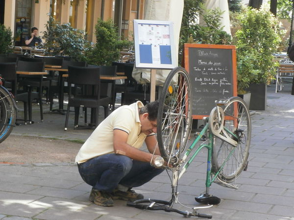 A man is repairing a bike in Strasbourg, France Alsace Bycicle City Life France Leisure Activity Lifestyles Man Showcase May Strasbourg Street Photography Travel Destination Street Portrait