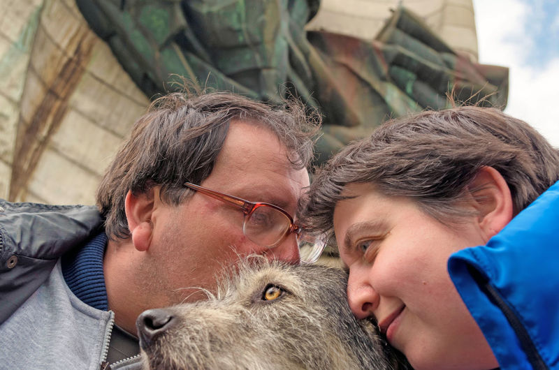 Close-up of couple kissing dog