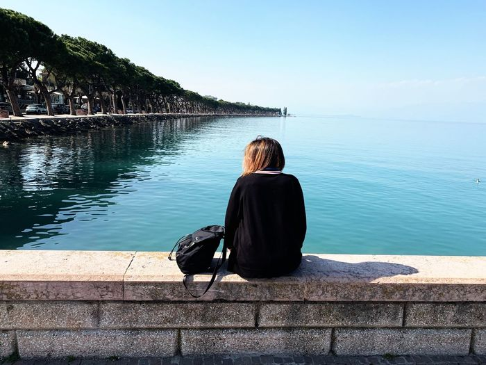 Rear view of woman looking at sea while sitting on retaining wall against sky