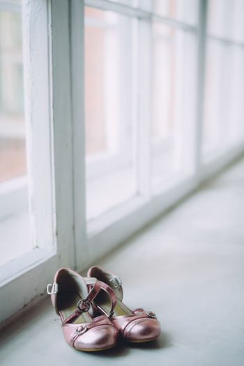 Close-Up Of Sandals On Floor By Window