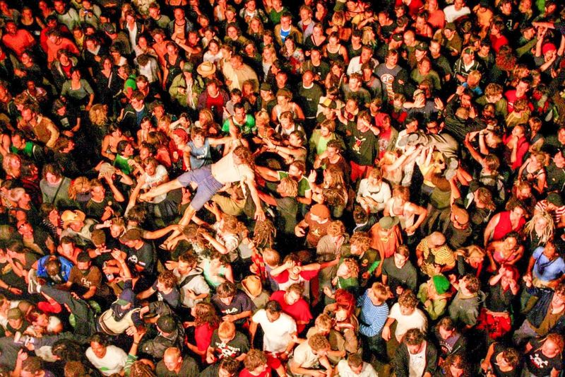 Men being carried by group of people during concert