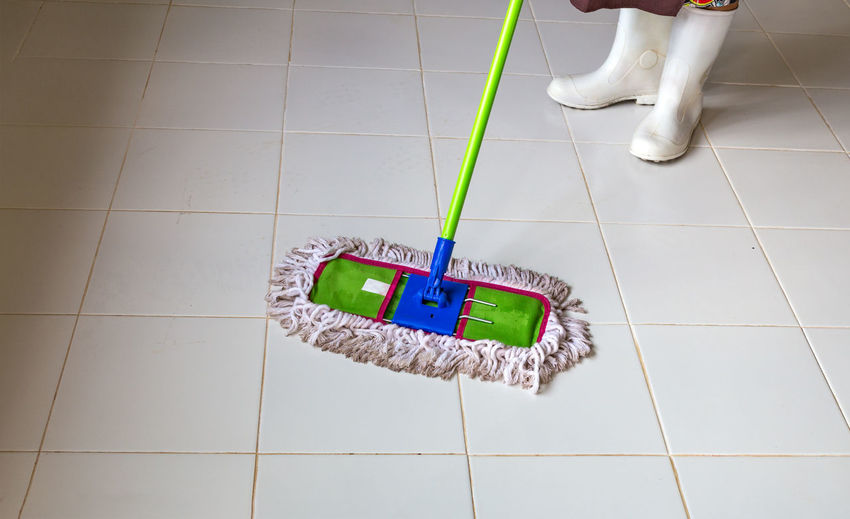 Low section of woman cleaning tiled floor with mop at home