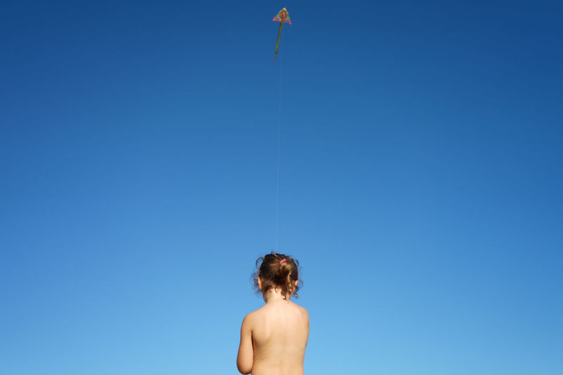 Rear view of young girl against clear blue sky