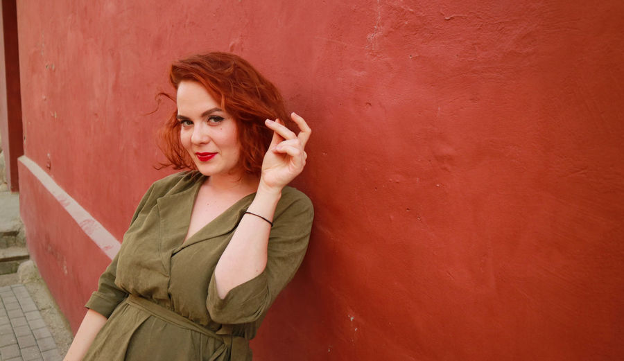 Portrait Of Smiling Woman Standing Against Red Wall