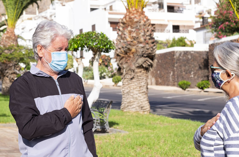 Senior couple wearing mask standing outdoors