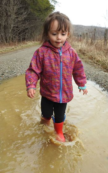 Cute Girl Standing In Puddle