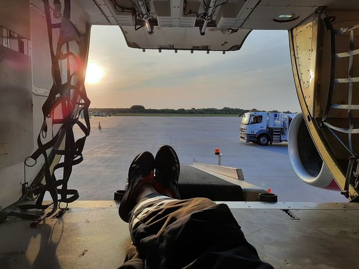 Low section of man in cargo hold against sky during sunset
