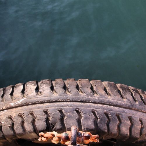 Close-up of cropped tire against water