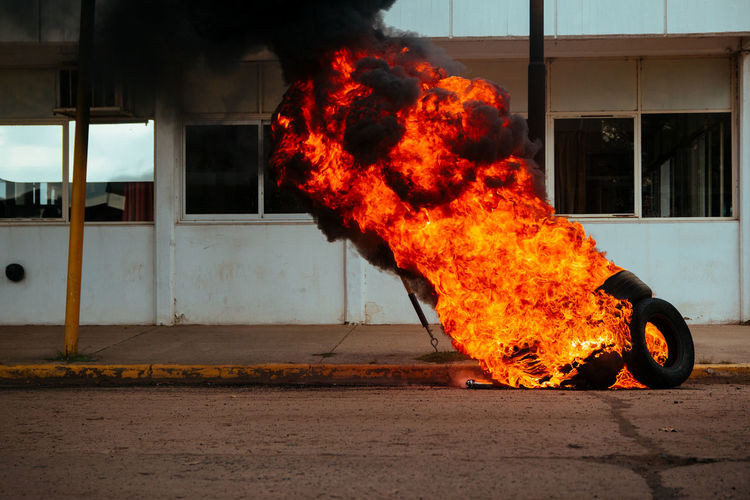 Burning vehicle on road against building