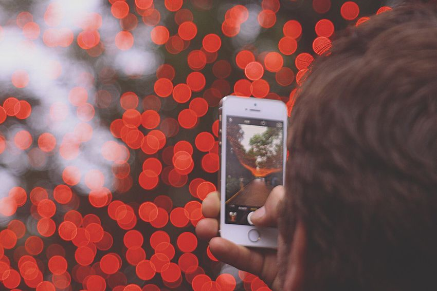 Focus Object Technology Mobile Phone Wireless Technology Photographing Photography Themes Holding Human Hand Communication Portable Information Device Smart Phone Real People Human Body Part Tree Close-up One Person Camera - Photographic Equipment Defocused Device Screen Digital Viewfinder Outdoors