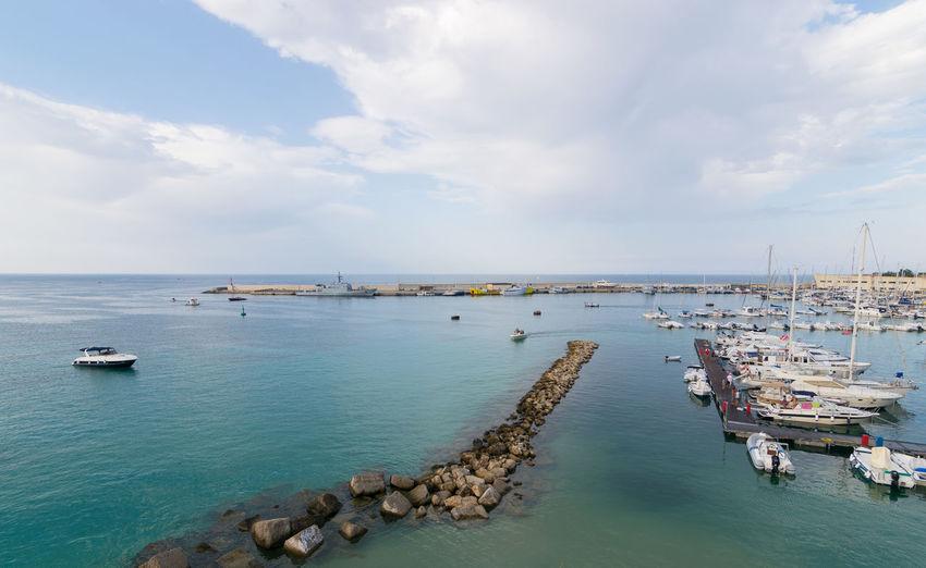 Sailboats Moored At Otranto Harbor Against Cloudy Sky