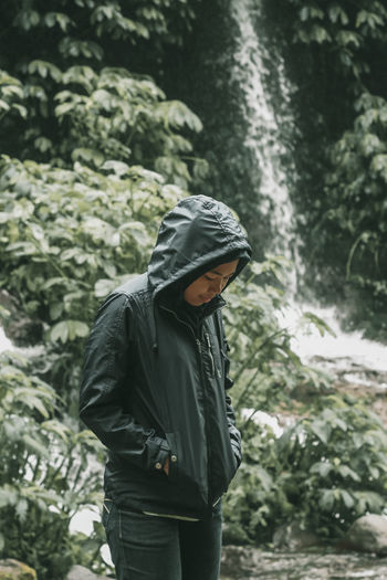 Young man standing against waterfall in forest