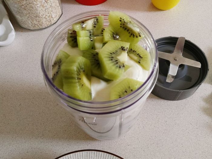 High Angle View Of Kiwi And Fruits In Container On Table