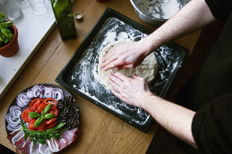 Midsection Of Man Kneading Dough