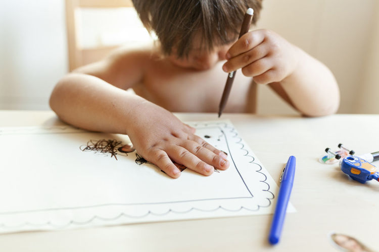 Midsection of boy making face on table