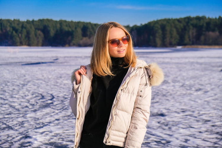 Young female smiling and away in sunglasses a snow landscape. happy hipster girl with hip hop