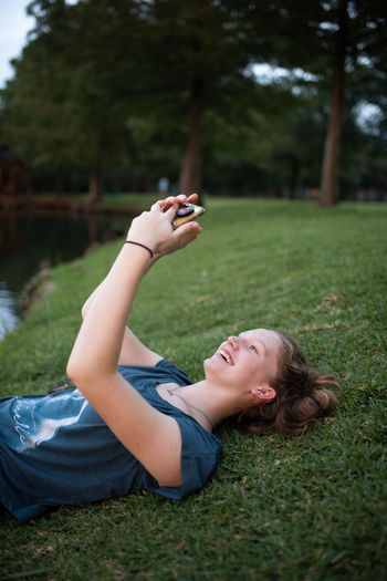 Young woman using mobile phone in field