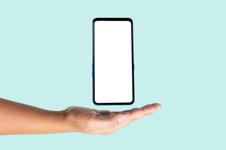 Midsection of man using mobile phone against white background