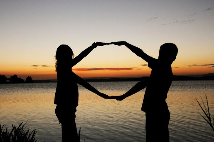 Silhouette of boy and girl making hand shape at lakeshore