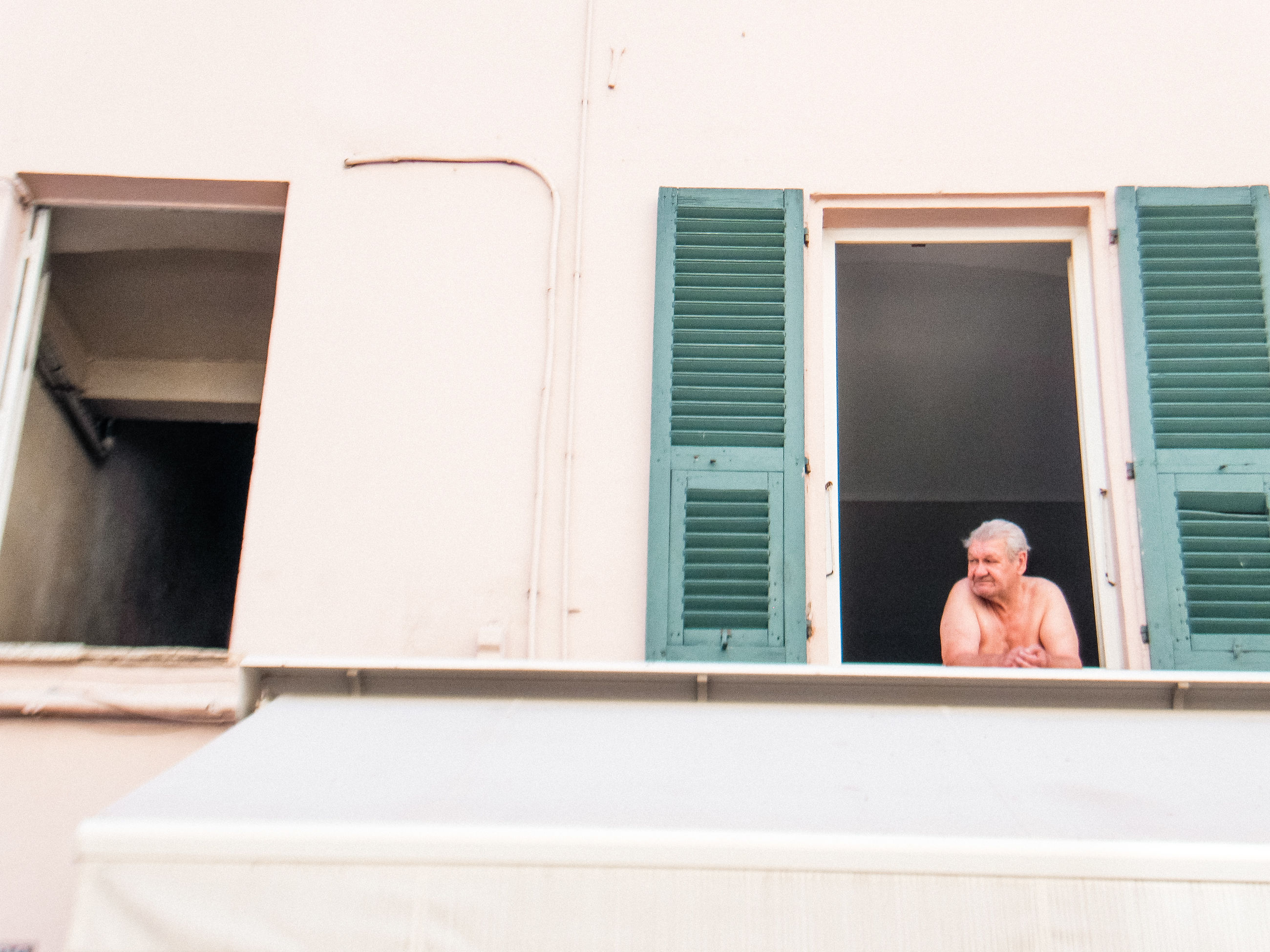 one person, real people, window, architecture, lifestyles, males, leisure activity, headshot, men, low angle view, relaxation, adult, built structure, day, portrait, front view, building exterior, looking, outdoors, mature men, contemplation