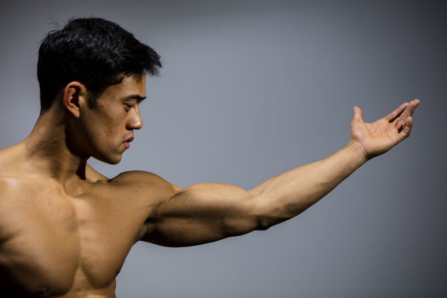 The muscular physique of a male fitness model put on display. Adult Asian  Athletic Body & Fitness Human Body Man Nam Vo Profile Shirtless Vietnamese Arms Spread Bicep Biceps Fit Fitness Model Grey Background Handsome Medium Close Up Model Muscles Open Hand Strong Toned Torso Upper Body