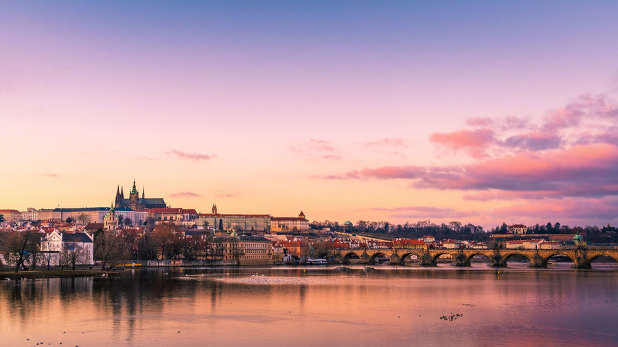Scenic view of river and buildings against sky during sunset