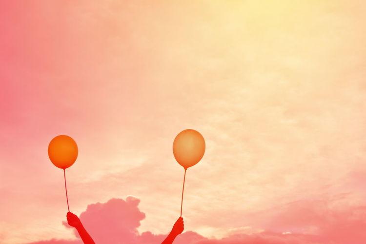 Balloons against orange sky