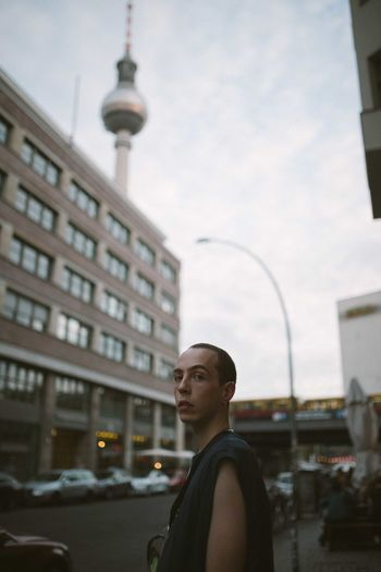 Man looking at city buildings against sky