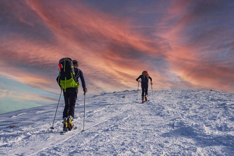 Rear view of people on snow against sky during sunset